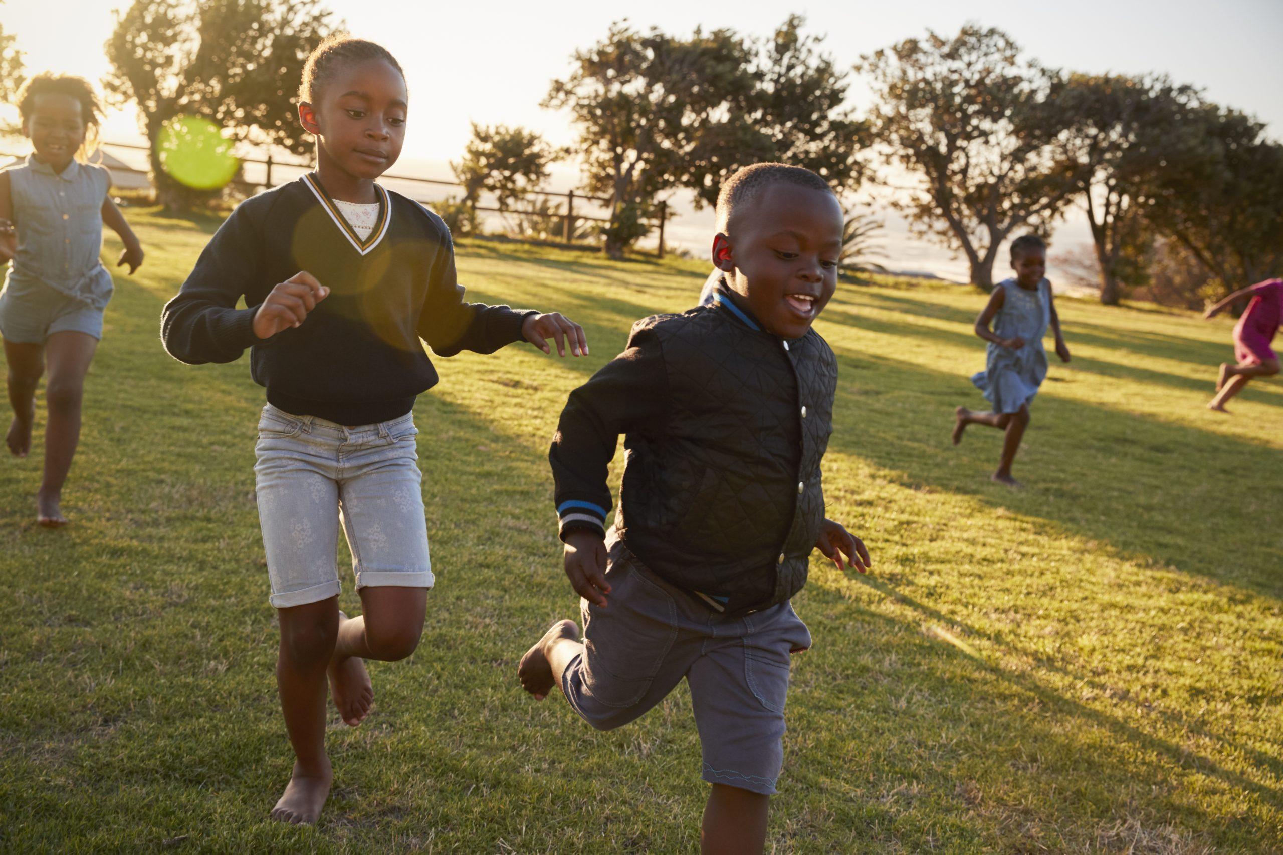 Elementary school kids running to camera in an open field